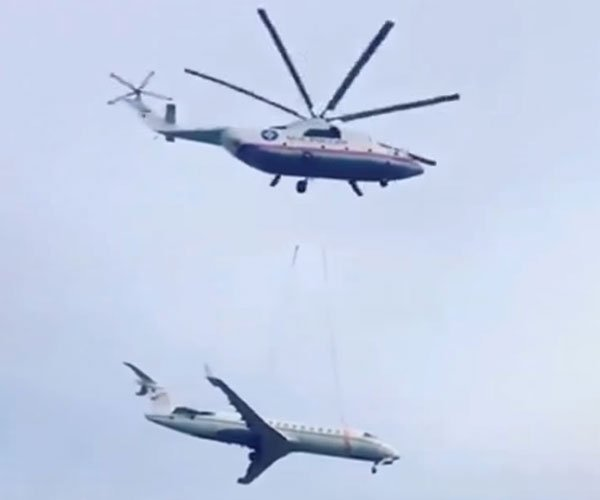 Helicopter Lifts a Jet Plane